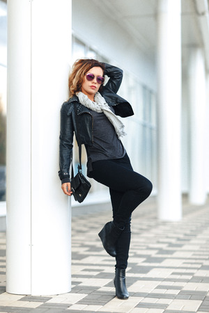 full-length portrait woman in sun glasses a black leather jacket, black jeans leans on a pillar holding up one leg in front of mirrored windows. Female fashion concept. Outdoor