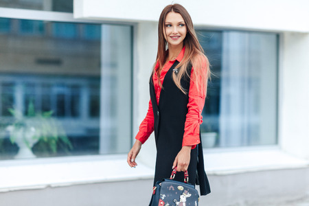 the happy young woman with long hair in a red shirt and a long sleeveless jacket walks down the street