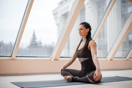 Middle aged yogi attractive woman practicing yoga concept, sitting in Half Lotus exercise, Siddhasana pose