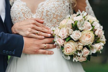 Bruidhanden met ring en huwelijksboeket Stockfoto