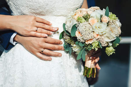 Bride hands with ring and wedding bouquet of flowers