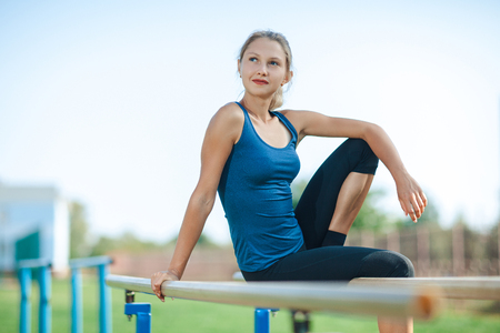 Beautiful young girl in a blue shirt and leggings sitting on the uneven bars, on the outdoor sports ground in summer looking at camera and smiling