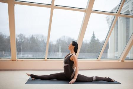 Young yogi woman practicing yoga concept, stretching in Monkey God exercise, Splits, Hanumanasana pose, working out, wearing black Stock Photo