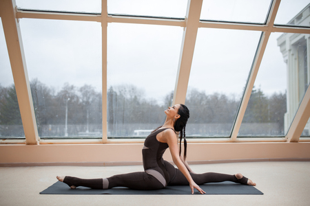 Yogi woman practicing yoga concept, stretching in Monkey God exercise, Splits, Hanumanasana pose, working out, wearing black sport