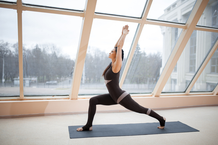 Middle aged woman standing in Warrior one exercise, Virabhadrasana I pose on the mat in front of large windows., exercise fitness,