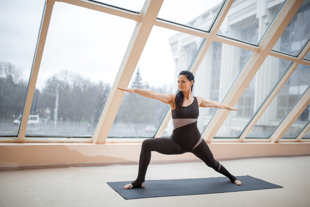Middle aged woman standing in Warrior two exercise, Virabhadrasana II pose on the mat in front of large windows., exercise fitness Stock Photo