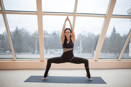 Yogi woman in a dark jumpsuit practicing yoga concept, standing in Sumo Squat exercise, Goddess pose, working out