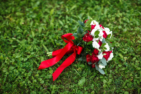 A bridal bouquet of a bride from white and red roses with red ribbon lies on a green grass