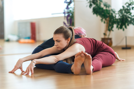 Two sporty girls in gym doing acroyoga, yoga with partner, Wide-Angle Seated Forward Bend, Upavishtha Konasana