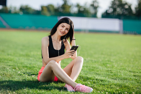 Young sporty joyful woman brunette in shorts and top sitting on the grass football field stadium and listens to music in earphones, her head thrown back, she gets pleasure, relaxes.