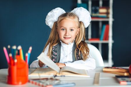 Child and school supplies home Schoolgirl at the table with a textbook and colorful stationery. Girl in school uniform at a Desk in the classroom, holding a textbook, looking at the camera and smiling.