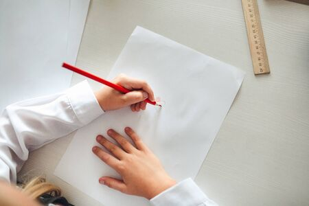 The childs hands are painted with colored pencils on a white sheet of paper on a wooden table.