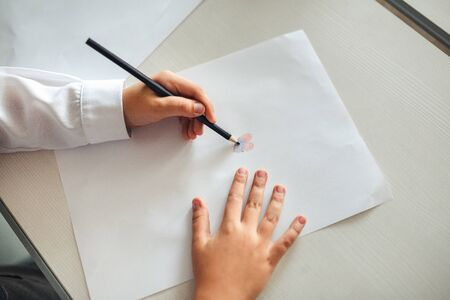 The childs hands are painted with colored pencils on a white sheet of paper on a wooden table