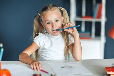 Pretty blondy girl thinking while doing her homework and holding a blue pencil, at home table