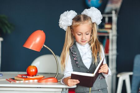schoolgirl blondy in school uniform with white bows standing near the table with red lamp and Apple and studying at home. Education and school concept