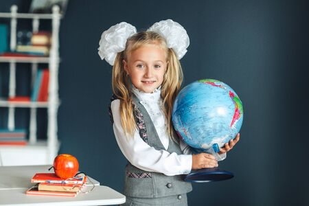 Cute blondy girl in school uniform with white bows with big globe in the hand look at camera and smiles at home, school and education concept