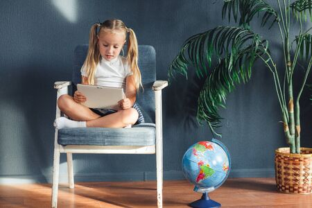 Pretty smiling blondy girl relaxing on a chair near the globe indoors at home with a tablet pc in her socks and jeans