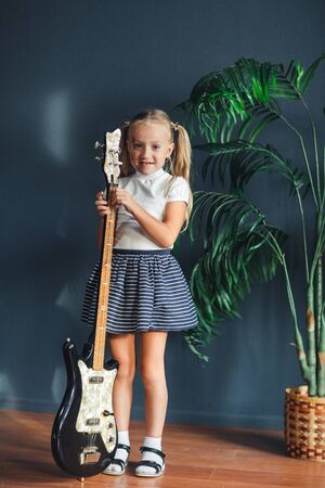young blonde girl with tails in white t-shirt, skirt and sandals with guitar at home
