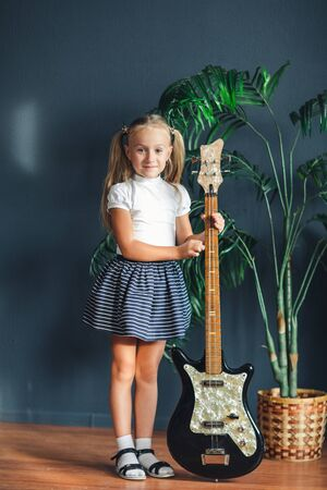 young blonde girl with tails in white t-shirt, skirt and sandals with electric guitar at home looking at camera and smiles