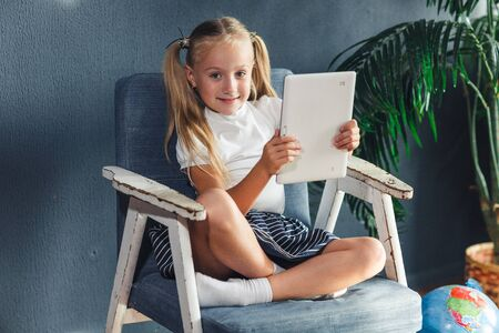 Technologies, people concept - young blondy girl sitting on a chair and watching the tablet or surfing the net and smiling