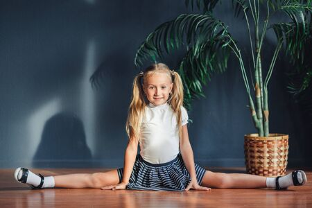 Beautiful little blonde girl with hair gathered in tails, white t-shirt, white socks and gray skirt sitting on twine at home looking at camera and smiles