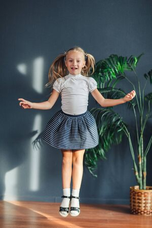 8 years old Beautiful little blonde girl with hair gathered in tails, white t-shirt, white socks and gray skirt jumping in a child room at home, still life photo