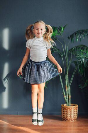 8 Jahre alt Schönes kleines blondes Mädchen mit in Schwänzen gesammelten Haaren, weißem T-Shirt, weißen Socken und grauem Rock, der zu Hause in einem Kinderzimmer springt, Stilllebenfoto
