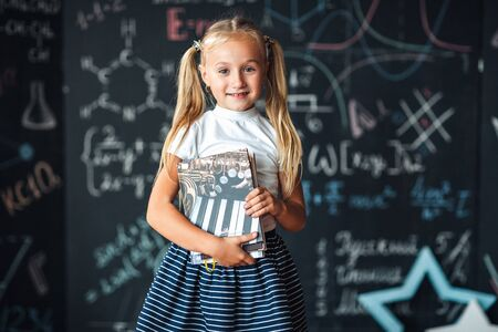 Smiling little blonde girl with hair gathered in tails, white t-shirt, and gray skirt is holding book in a classroom with a chalkboard covered with formulas and figures.