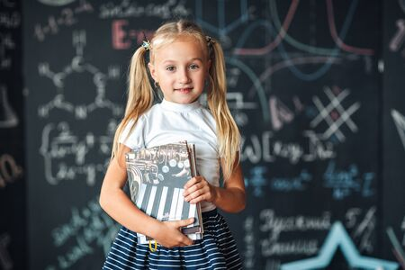 Smiling little blonde girl with hair gathered in tails, white t-shirt, and gray skirt is holding book in a classroom with a chalkboard covered with formulas and figures