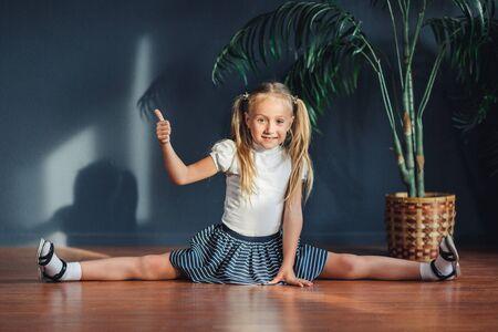 Aptitud joven hermosa chica haciendo deporte ejercicio y sentarse en divisiones cordeles en estera de yoga en la mañana. Estilo de vida saludable, concepto de entrenamiento matutino