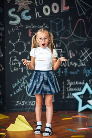 Little blonde girl with a surprised face with a ruler in her hands Pupil girl with big rulers against chalkboard with school formulas. back to school. Schoolgirl learning geometry. math lesson 스톡 콘텐츠
