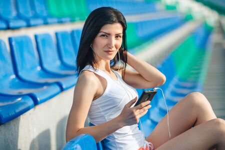 Young brunette sport girl posing at stadium. Fitness girl in shorts and tank top sitting on the blue seats at the stadium, listen to music on your smartphone, relax. looking at the camera and smiling. 스톡 콘텐츠
