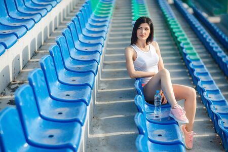 Portrait of Young brunette sport girl with water bottle. Fitness girl in shorts and tank top sitting on the blue seats at the stadium, relax. Sport and healthy lifestyle.