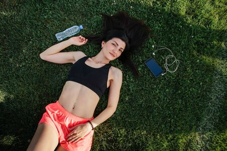 Portrait of a happy young fitness brunette woman lying on the football pitch with a bottle of water and a smartphone after workout and smiling.