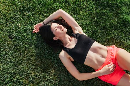 Portrait of a happy young fitness woman laughing and resting on grass after workout and smiling. Sport in open air and health care concept. 스톡 콘텐츠