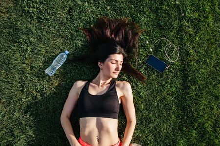 Portrait of a happy young fitness brunette woman lying on the football pitch after workout and smiling. Sport in open air and health care concept,