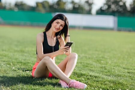 Young sporty joyful woman brunette in shorts and top sitting on the grass football field stadium and listens to music in earphones, she gets pleasure, relaxes. Girl after a hard workout.