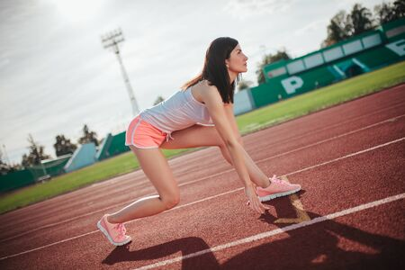 side view Athletic woman on running track getting ready to start run, Amateur athlete