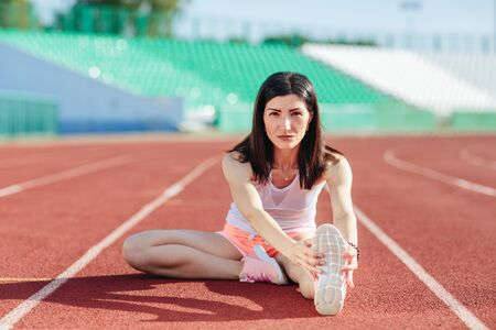 Young woman athlete on stadium sporty lifestyle sitting on track stretching legs bending down looking camera smiling cheerful.