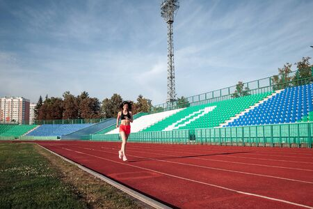 Full body of girl running track on stadium. Real front view of young woman in pink shorts and tank top and pink sneakers. Outdoors, sport.