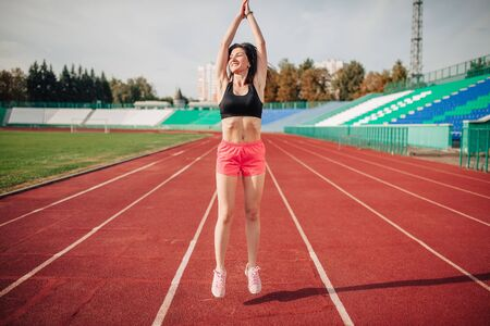 Attractive sporty woman doing workout with jump rope in sun rays 스톡 콘텐츠