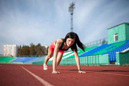 Young woman athlete on stadium sporty lifestyle doing push ups on track looking aside concentrated close-up