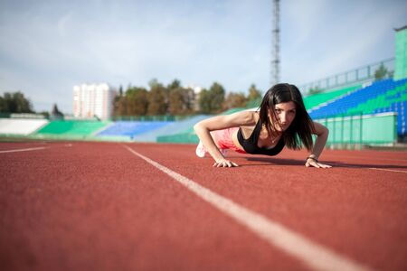 young fitness woman runner push up on stadium track