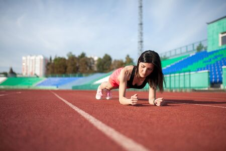 Beautiful and athletic girl push ups at the stadium 스톡 콘텐츠