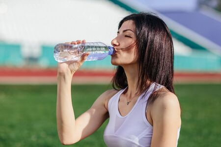 young pretty brunette Caucasian girl in pink shorts and tank top in suit resting after sport run in the park on football stadium on grass drinking water and smiling enjoying.