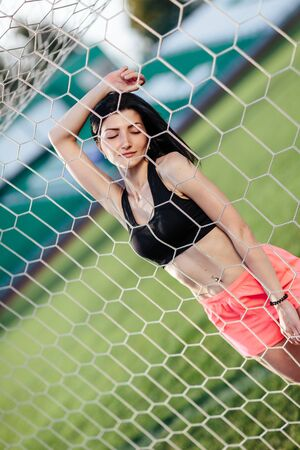 Front view of sexy woman hold ball in hand after penalty kick. Goalkeeper stand in gate behind stadium with seat on background. Female sport idea.