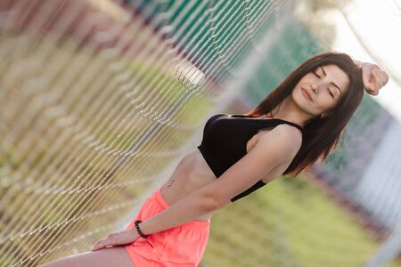 Beautiful stylish brunette woman with closed eyes in black top and pink shorts stands near a football goal at the stadium at sunset. Beautiful sunlight. A girl with a perfect figure and in great shape
