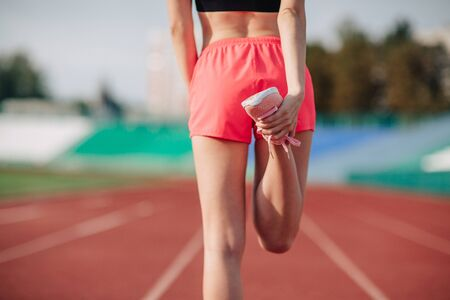 Young woman athlete in pink shorts and topon stadium sporty lifestyle standing stretching leg back view close-up.