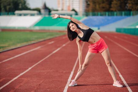 Athlete Attractive sporty brunette woman in pink shorts and top exercise stretching at sport stadium in evening, sunset. Sport and healthy lifestyle.