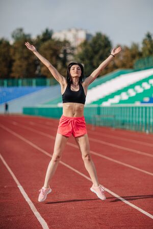 Attractive sporty brunette woman in pink shorts and top doing workout with jump rope in sun rays at the stadium.